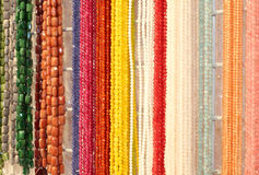 Many shimmering necklaces made with colorful stones for sale in Royalty Free Stock Images