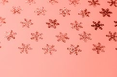 Many shimmering snowflakes on a coral background stock photos