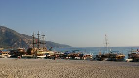 Many ships on seaside. Different ships boats and yachts on the seaside in Fethie Turkey with mountain on background Stock Photos