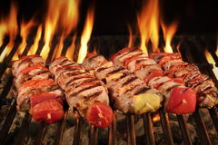 Many Shish Kebab On The BBQ Flaming Charcoal Grill. Many Shish Kebab From Different Meat With Pepper And Tomato On The Hot Charcoal BBQ Grill With Bright Flames Stock Image