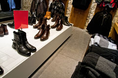 Many shoes and clothes on shop store shelves Royalty Free Stock Images