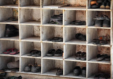 Many Shoes in Cubby Holes at Entrance to Hindu Temple. Many pairs of shoes, arranged in old, scuffed and worn cubby holes near the entrance to a Hindu temple in stock image