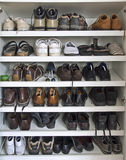Many shoes on shelves. In a closet stock photography