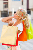 Many Shoping Bags Held by Girl. Blond girl with lot of bags smiling cutely royalty free stock photos
