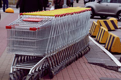 Many shopping carts for shopping are standing on the street near a busy intersection. Stock Image