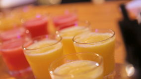 Many shot glasses with alcohol and citrus fruits juice stock video