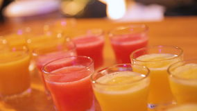 Many shot glasses with alcohol and citrus fruits juice stock video footage