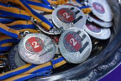 Many silver medals with blue ribbons on a silver tray, awards of champions, sport achievements, second place, prize for the winner.  Stock Photography