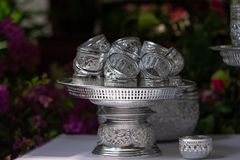 Many silver water bowl on silver tray for using pour sacred water to older people in Songkran festival. New year tradition of Thai people stock images