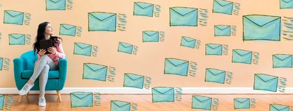 Many sketch emails with woman using a tablet stock image