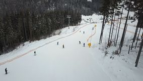 Many skiers and snowboarders descend down the ski slope stock video