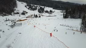 Many skiers and snowboarders descend down the ski slope stock footage