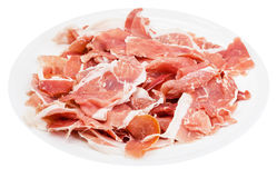 Many slices of dry-cured ham on plate isolated Stock Photo