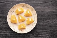 Many slices of orange on a black wooden table in a brown dotted plate royalty free stock photo