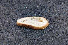 A lot of bread is lying on the asphalt, spoiled bread, hunger. Many slices of stale bread and other stale baked goods. A lot of bread is lying on the asphalt royalty free stock photography