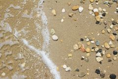 Many small beautiful stones on a sandy summer beach. The wave rolls on the stones royalty free stock photography