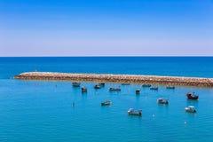 Many small boats lying near jetty in sea royalty free stock photo
