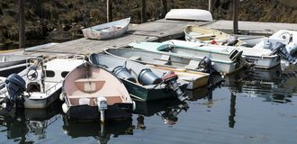 Small boats tied to dock and each other in Maine Royalty Free Stock Image