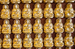 Many small Buddha statue on the wall at chinese te Stock Images