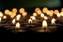 Many small burning candles. On a wooden surface royalty free stock image