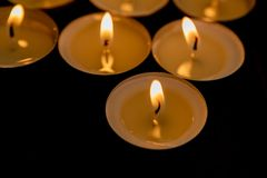 Many small burning candles. On a wooden surface royalty free stock photography