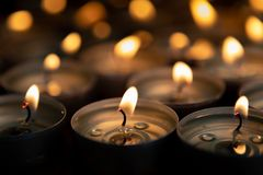 Many small burning candles. On a wooden surface royalty free stock photos