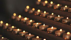 Many small church candles burn at the altar. In Catholic Church