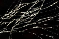 Many small cracks on the surface of the glass, a broken screen of a mobile phone. Abstract background stock photos