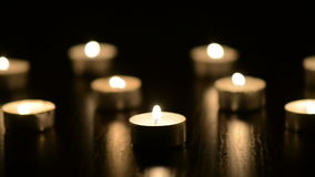 Many small flaming candles on black tabl stock footage