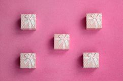 Many small gift boxes in pink color with a small bow lies on a blanket of soft and furry light pink fleece fabric. Packing for a g. Ift to your lovely girlfriend royalty free stock image