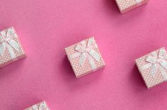 Many small gift boxes in pink color with a small bow lies on a blanket of soft and furry light pink fleece fabric. Packing for a g. Ift to your lovely girlfriend royalty free stock photography