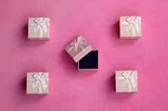 Many small gift boxes in pink color with a small bow lies on a blanket of soft and furry light pink fleece fabric. Packing for a g. Ift to your lovely girlfriend royalty free stock photos