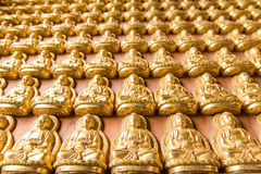 Many of small golden Buddha statue on the wall at chinese temple Royalty Free Stock Photography