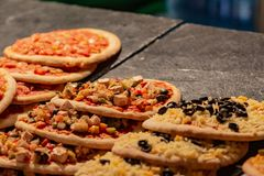 Many small hot pizzas on sale at a street market royalty free stock image
