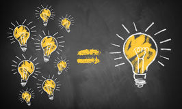 Many small ideas leading to the big picture. Symbolized by lightbulbs drawn on a chalkboard Royalty Free Stock Images
