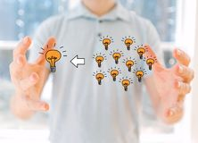 Many small ideas into one big idea with young man. Holding his hands royalty free stock image