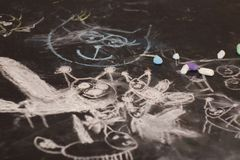 Sketch flock of lynx on the blackboard. Many small and large cats are drawn with chalk on a black chalk surface by the hand of a child. Children`s sketch flock royalty free stock images