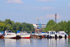 Many small modern motorboats at pier on river Stock Images