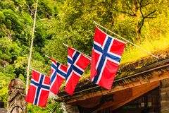Many small Norway flags in row outdoor. Many small Norway flags in row, green natural forest in background outdoor shot. National symbols, patriotism concept royalty free stock photo
