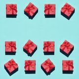 Many small red pink gift boxes on texture background of fashion trendy pastel blue color paper in minimal concept. Abstract. Pattern stock photography