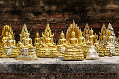Many small yellow statue buddha beside the old brick wall in the Temple, Thailand.  royalty free stock image