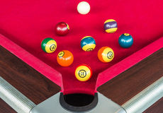 Many snooker balls or pool balls near the corner hole on red table Stock Photo