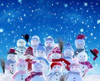 Many snowmen standing in winter Christmas landscape. royalty free stock photos