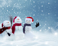 Many snowmen standing in winter Christmas landscape. Merry Christmas and happy New Year greeting card with copy-space.Many snowmen standing in winter Christmas Royalty Free Stock Images