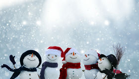 Many snowmen standing in winter Christmas landscape. Merry Christmas and happy New Year greeting card with copy-space.Many snowmen standing in winter Christmas Stock Images