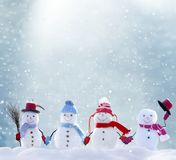 Many snowmen standing in winter Christmas landscape stock images