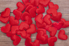 Many soft red hearts scattered on a wooden Board Royalty Free Stock Photos
