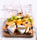 Many sorts of cheese with fruits. Over wooden board Stock Images