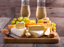 Many sorts of cheese with fruits. Over wooden board Stock Photos
