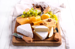 Many sorts of cheese with fruits. Over wooden board Stock Photography
